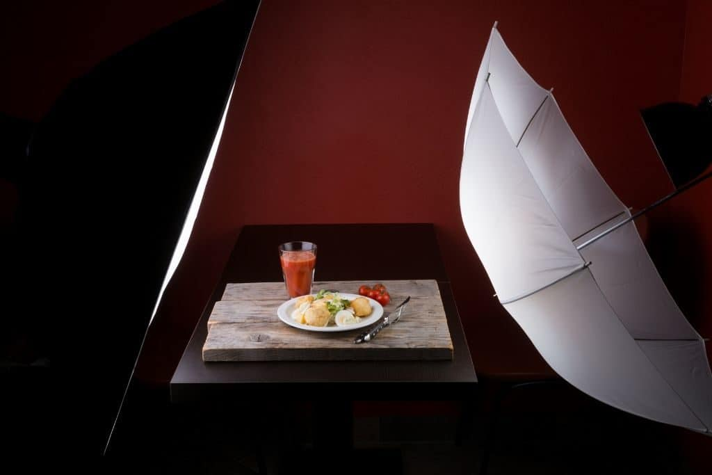 An artificial light source next to a plate of food and a drink next to a photography umbrella