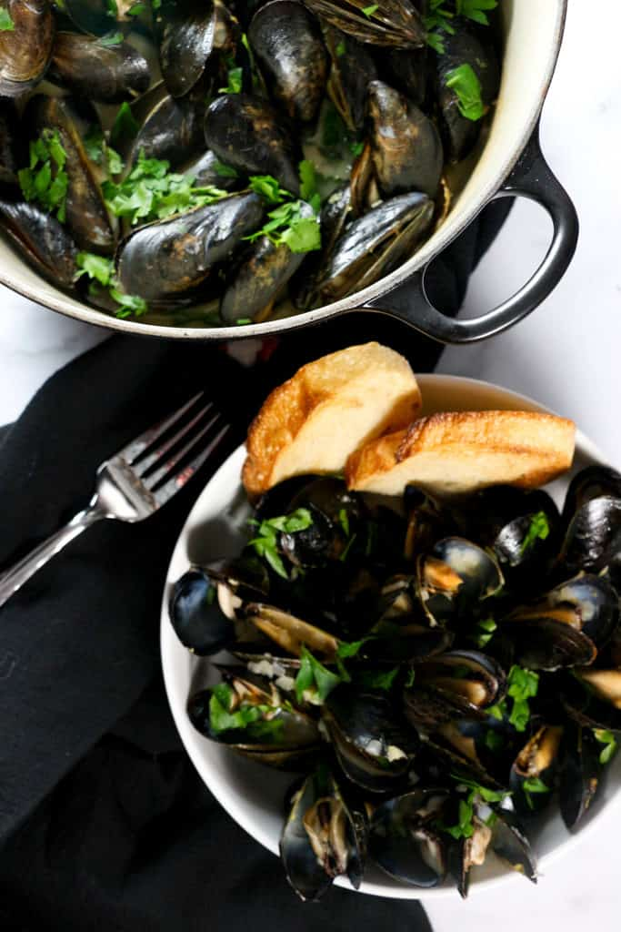 A pan of mussels with a plate full of mussels and bread
