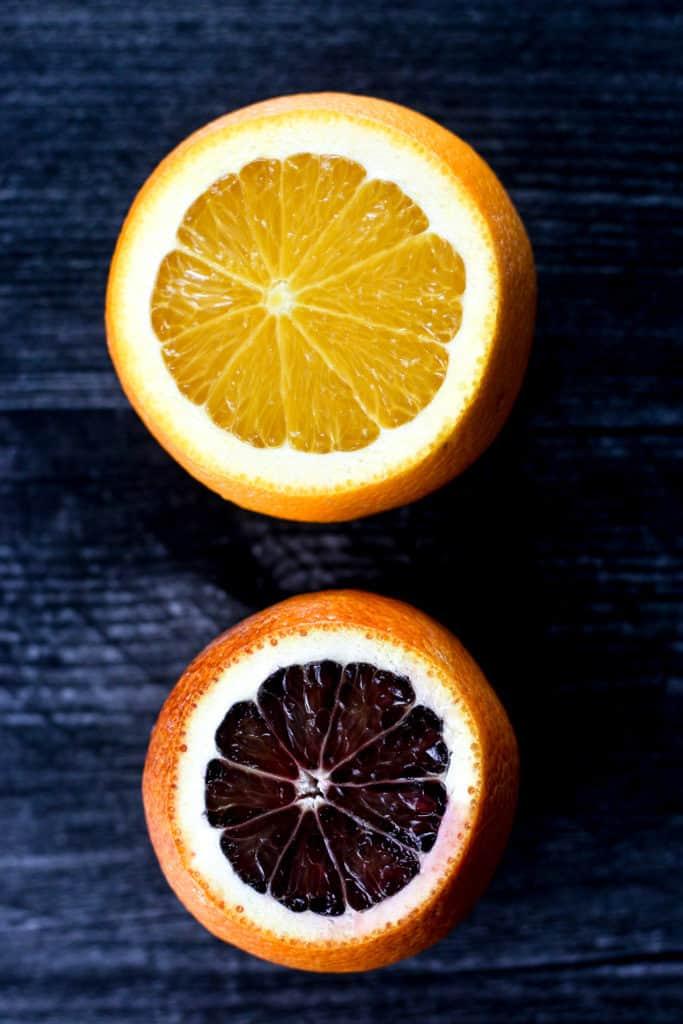 A regular orange next to a moro blood orange
