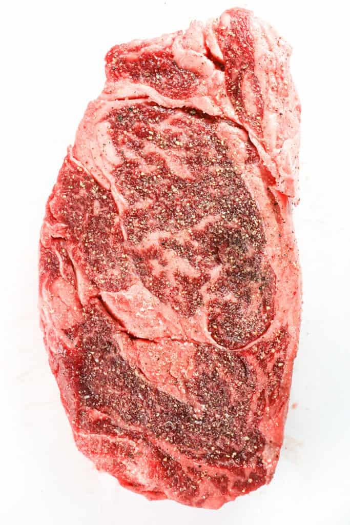 A raw ribeye steak on a white surface